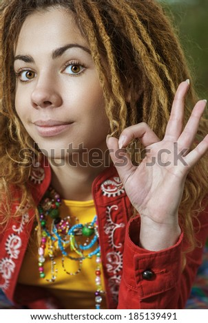 Young smiling beautiful woman with dreadlocks in red clothes making sign of fingers all ok. - stock photo