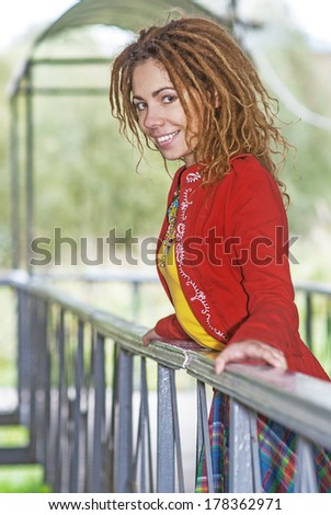 Young smiling beautiful woman with dreadlocks in red clothes near wooden railing. - stock photo