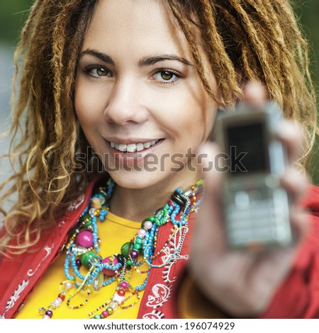 Young smiling beautiful woman with dreadlocks in red clothes showing mobile phone. - stock photo