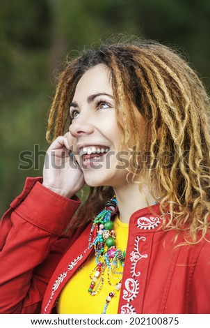 Young smiling beautiful woman with dreadlocks in red clothes talking on mobile phone. - stock photo