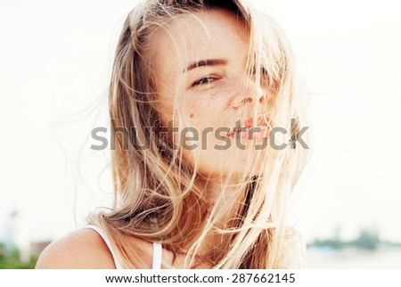 Young Smiling Beautiful Woman with Hair Blowing in the Wind. Toned - stock photo