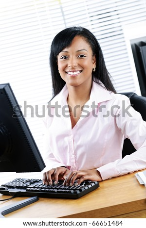 Young smiling black business woman at desk typing on computer - stock photo