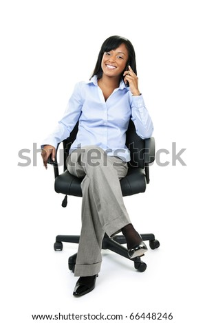Young smiling black businesswoman on phone sitting in leather office chair - stock photo