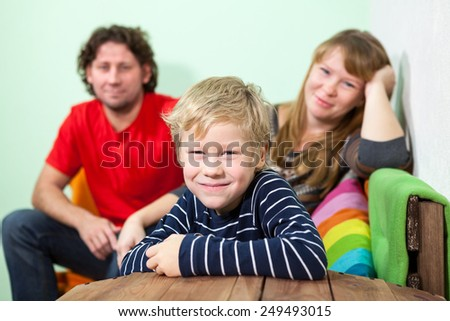 Young smiling blond hair son sitting on foreground of his parent on the sofa - stock photo