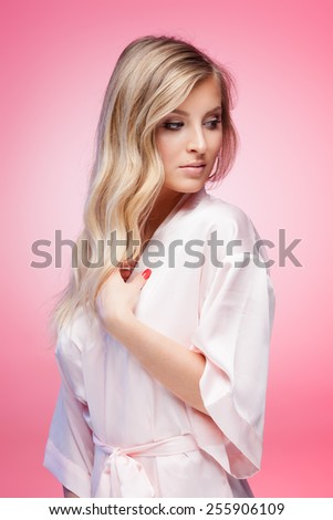 Young smiling blond lady wearing a sexy bathrobe on pink background - stock photo