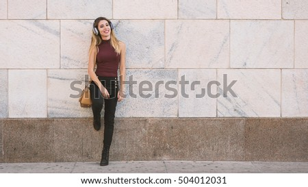 Young smiling blond woman relaxing listening to music with earphones in the city against plain wall. Milan, Italy. Lifestyle concept of youth, fun, enjoy life.