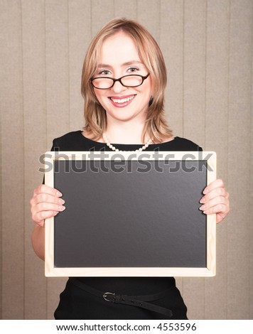 Young smiling blond woman teacher in black dress and pearls, wearing glasses with empty blackboard - stock photo