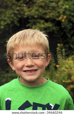 Young smiling blonde boy with a gap in his teeth