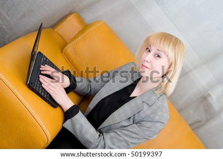 young smiling blonde woman sits on sofa with laptop - stock photo