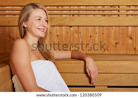 Young smiling blonde woman sitting in a sauna - stock photo
