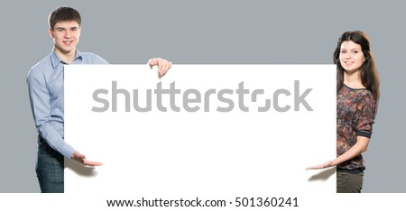 Young smiling boy and girl with white placard. Studio. Isolated on light gray background.