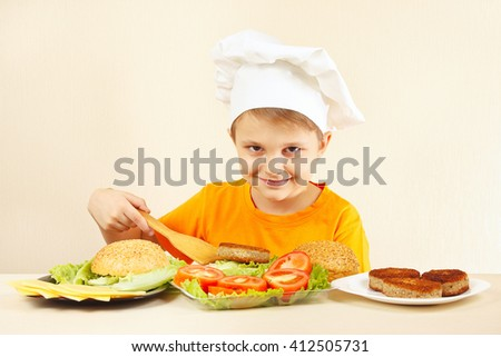 Young smiling boy in chef hat puts meat on the hamburger - stock photo