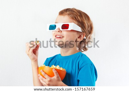 Young smiling boy in stereo glasses eating popcorn on white background - stock photo