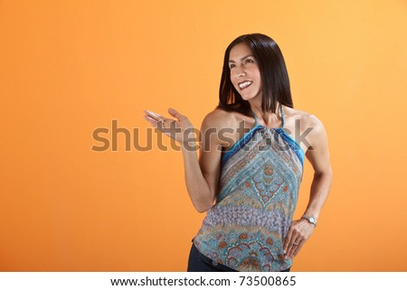 Young smiling brunette an orange background with palm facing up - stock photo