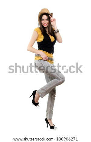 Young smiling brunette in stetson standing on one leg. Isolated on white - stock photo