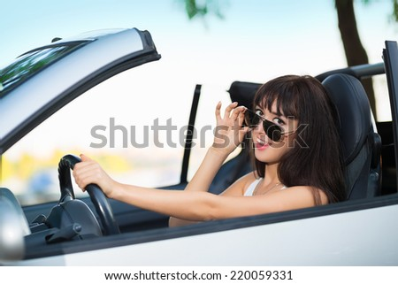 Young smiling brunette posing in grey car with sunglasses - stock photo
