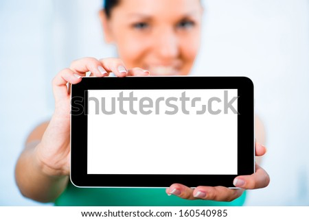 young smiling brunette woman holding a touch pad with a white screen close to the camera - stock photo