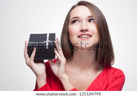 Young smiling brunette woman holding gift - stock photo