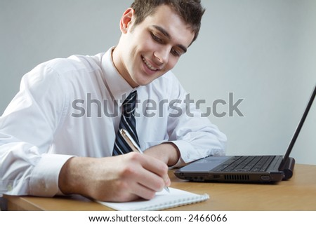 Young smiling business man or student with laptop at the table, working