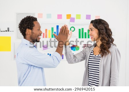 Young smiling business people clapping hands in the office - stock photo