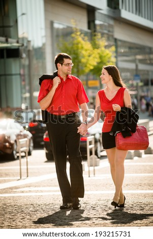 Young smiling business people in red walking street after their work - stock photo