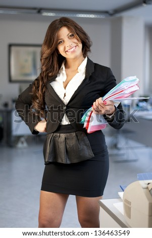 Young smiling business woman holding documents on office background