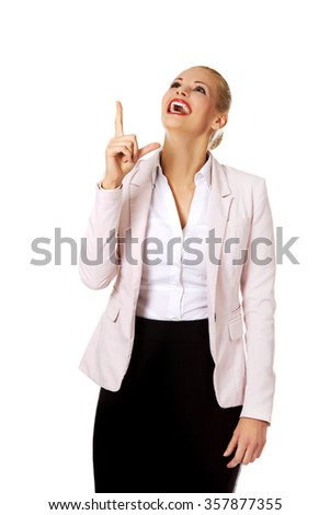 Young smiling business woman pointing up.