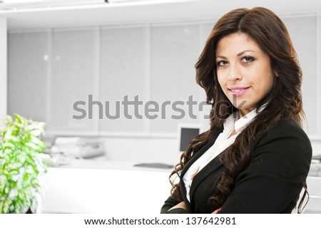 Young smiling business woman posing on office background - stock photo