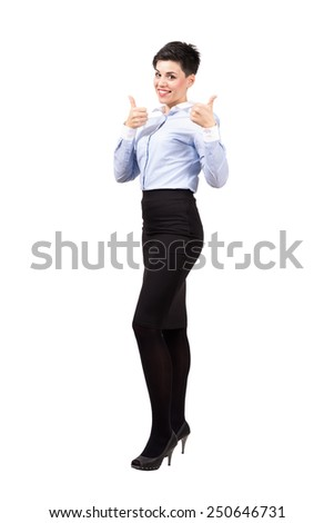 Young smiling business woman showing thumbs up gesture looking at camera. Full body length portrait isolated over white background.