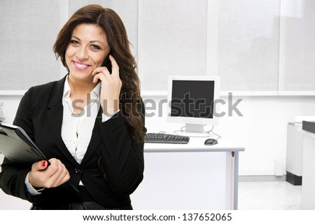 Young smiling business woman talking at the phone on office background - stock photo