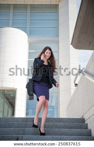 Young smiling business woman walking on stairs calling with mobile phone - stock photo
