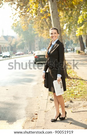 young smiling business woman with newspaper standing on street - stock photo