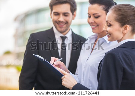 Young smiling business women and business man. three people looking at folder outside - stock photo