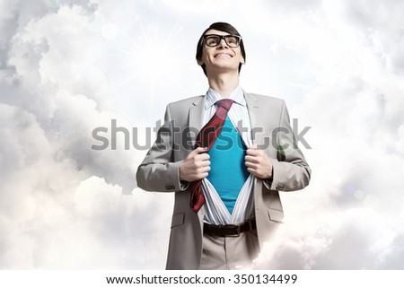Young smiling businessman acting like super hero and tearing his shirt off - stock photo