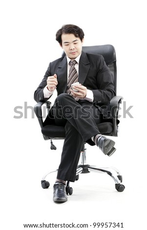 Young smiling businessman calling on phone at office. - stock photo