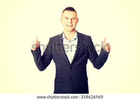 Young smiling businessman gesturing thumbs up. - stock photo