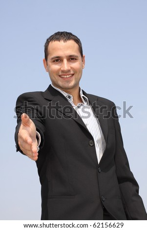 Young smiling businessman giving hand for an handshake with focus on a face at blue sky background