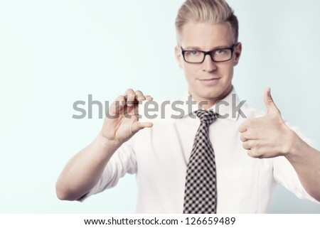 Young smiling businessman giving thumbs up at white blank business card with space for text while holding it, isolated. - stock photo