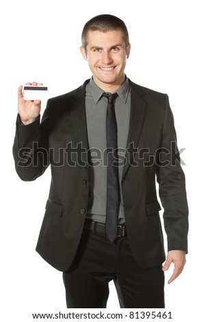 Young smiling businessman holding credit card, isolated on white background - stock photo