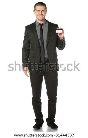 Young smiling businessman holding credit card, isolated on white background