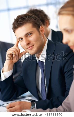 Young smiling businessman holding hand near head in the office with colleagues.
