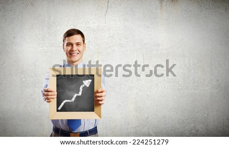 Young smiling businessman holding wooden frame with graph - stock photo