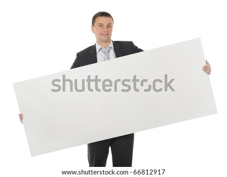 Young smiling businessman in black suit holding large blank. Isolated on white background - stock photo