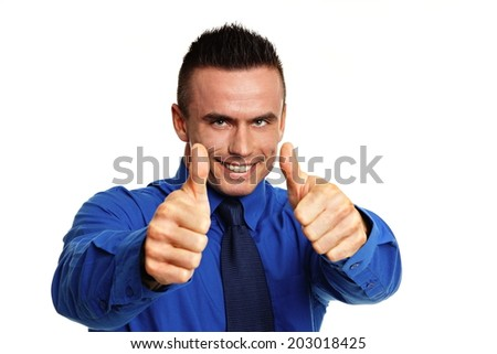 Young smiling businessman in blue shirt shows you thumbs up