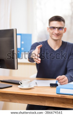 Young smiling businessman in glasses holds out his hand for a handshake at his workplace - stock photo