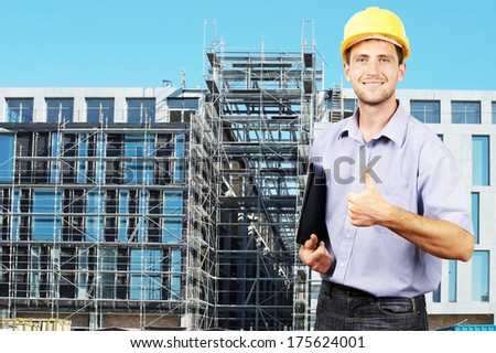 Young smiling businessman in his helmet against the backdrop of the building under construction - stock photo
