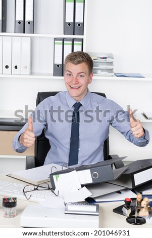 Young smiling businessman is holding both thumbs up despite of chaos on his desk in the office. A shelf is in the background. The man is looking to the camera.