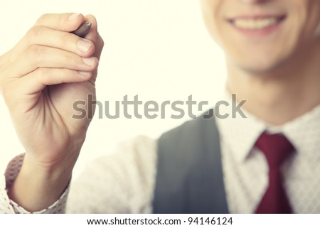 Young smiling businessman is writing on a virtual whiteboard. Focus is on the hand and pen - stock photo