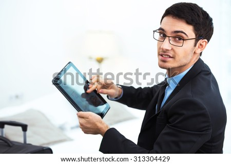 Young smiling businessman looking at camera and using tablet computer while sitting in cozy hotel room with suitcase - stock photo