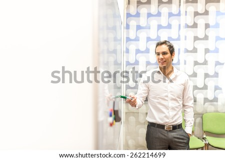 Young Smiling Businessman Looking Confident While Giving Presentation at Board in Modern Office Conference Room. - stock photo